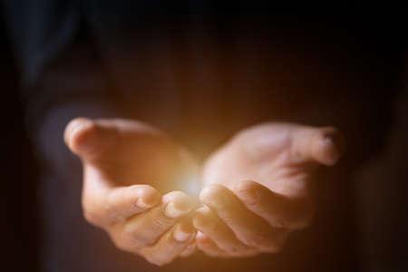 Man hands praying in dark
