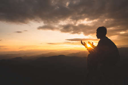 Silhouette of young  man hands open palm up worship and praying to god  at sunrise, Christian Religion concept background.