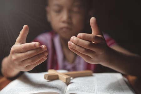 Religious Christian Child  praying over Bible indoors, Religious concepts. Religious beliefs Christian life crisis prayer to god.