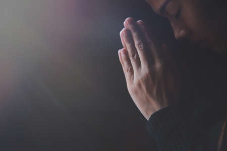 Praying hands with faith in religion and belief in God on dark background. Pay respect.  Namaste or Namaskar hands gesture. 스톡 콘텐츠