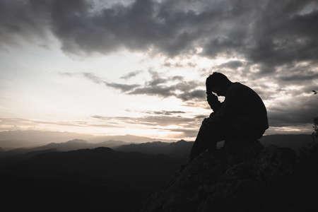 Sad man silhouette worried on the mountain. Drug addiction, failure concept.