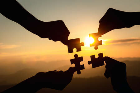 Silhouette  hands connecting  jigsaw puzzle piece against sunrise, Business solutions,  teamwork, partnership, success, goals and strategy concepts. 스톡 콘텐츠