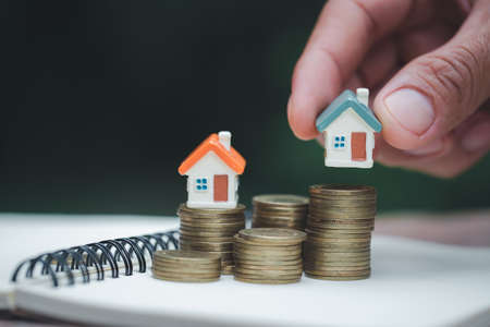 A woman holding a house on a pile of coins is planning savings money. concept for property ladder, mortgage and real estate investment. for saving or investment for a house. 스톡 콘텐츠
