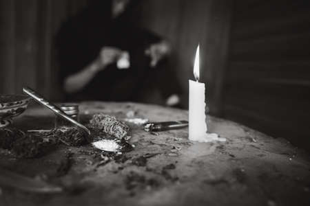 Drug addicts in the dark room. Addict/junkie preparing drugs with a spoon and lighter. White powder and a syringe. Drug concept. International drug abuse day.