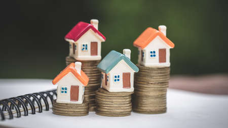 Model house on stack of coins. Saving money for home purchase, mortgage and real estate investment.