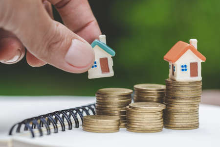 Investors hold houses and money, Real estate,  Property investment and house  Mortgage concept by money house from the coins.