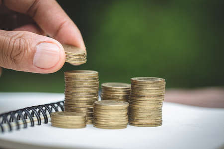 Human hand  putting coins money stack step growing growth saving money, deposit Close up of person hand stacking golden coins, Concept finance business investment.
