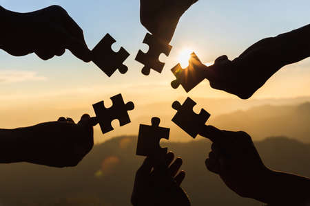 Silhouette of hand holding Jigsaw with Sunrise background. . symbol of association and connection. business strategy.
