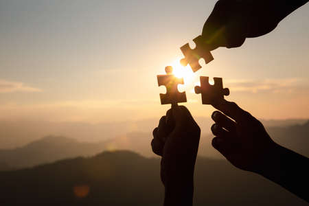 Silhouette  hands connecting  jigsaw puzzle piece against sunrise, Business solutions,  teamwork, partnership, success, goals and strategy concepts. Reklamní fotografie