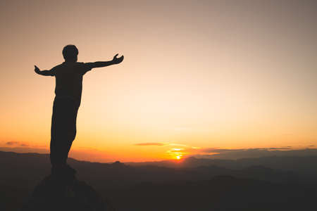 Man rise hand up on top of mountain and sunset,  Freedom and travel adventure concept. Religious beliefs, Copy space.
