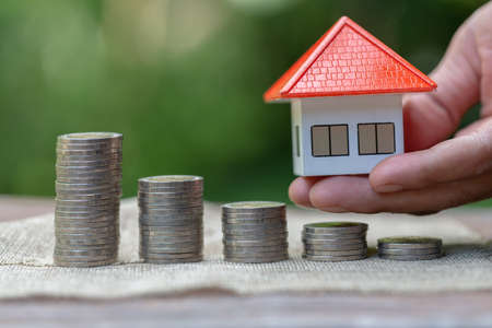 Real estate investors hold home models in hands. Saving plan to buy property, house. Personal financial concept for own a house. coin stack on wood table. copy space.