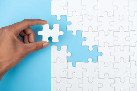 Closeup hand of woman connecting jigsaw puzzle, Business solutions, success and strategy concept. 版權商用圖片