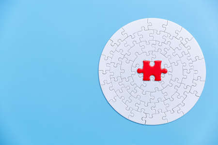 White and red jigsaw puzzle on a blue background. Copy space for text, top view, close up.