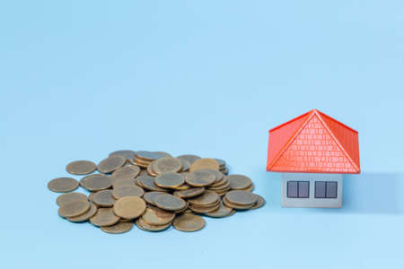 Coin stacks and house model, mortgage and real estate investment, for saving or investment for a house.