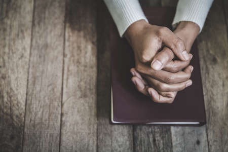 Hand of woman while praying for christian religion, Casual woman praying with her hands together over a closed Bible.