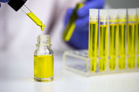 Hemp oil research, Researcher holding a dropper with hemp oil product. CBD cannabis oil. medical marijuana concept.