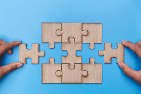 Hand of woman connecting jigsaw puzzle, Business solutions, success and strategy, Business partnership concept.