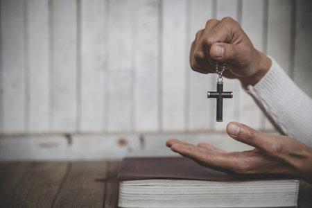 Hands holding wooden cross  on sunrise background, Crucifix, Symbol of Faith. 免版税图像