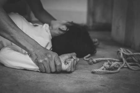 Depressed teenager sitting holding head in hands, stressed sad young woman having mental problems, Abusive and rape, Domestic Violence and Trafficking 免版税图像