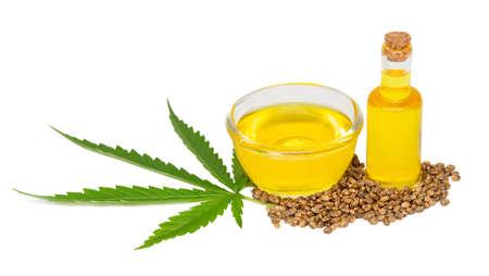 Cannabis (marijuana, hemp) oil in a glass cup and cannabis seeds isolated on white background, cbd,  medical marijuana concept. 免版税图像