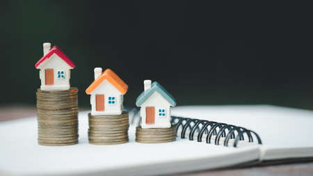 Mini house on stack of coins,Money and house,  Mortgage, Savings money for buy house and loan to business investment for real estate concept. Invesment and Risk Management, isolated.