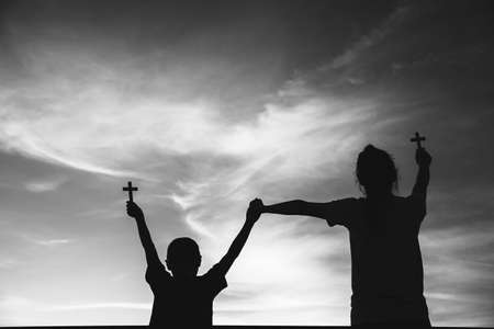 Two children worship God by holding christian Cross, christian concept. 免版税图像