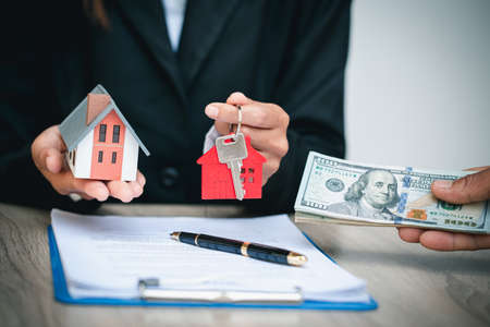 Agents are giving house keys of customer and holding dollar us. Agreement and Real estate concept. 版權商用圖片