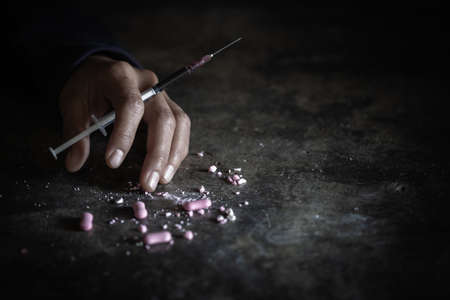 Human hand of a drug addict and a syringe with narcotic syringe lying on the floor. Anti drug. male drug addict, drug syringe.