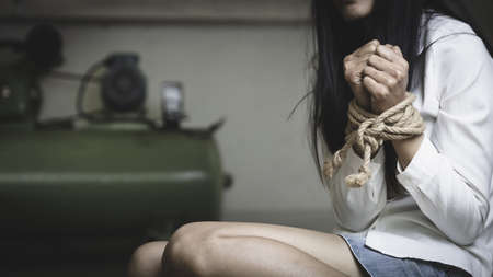 Hands tied up with rope of a missing kidnapped, abused, hostage, victim woman in pain, Human trafficking and rape concepts. 版權商用圖片