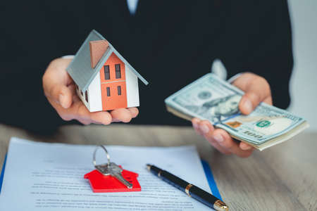 Real estate agent showing new house and bank note from Saving account for home insurance. House purchase contract. 版權商用圖片