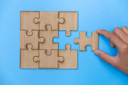 Hand put the last piece of jigsaw puzzle on  blue background to complete the mission,   Team business concept