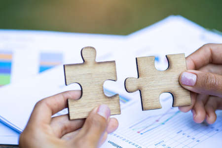 Two hands of businessman to connect couple puzzle piece. symbol of association and connection. business strategy. 版權商用圖片