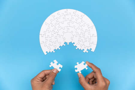 Two hands of businessman to connect couple puzzle piece. symbol of association and connection. business strategy. Banque d'images