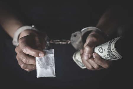 Drug dealer under arrest confined with handcuffs.   Anti drug.  Drug concept. 版權商用圖片