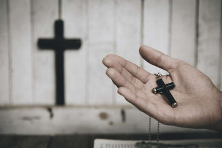 Woman hands holding wooden cross praying in the church,  spirituality and religion.  vintage tone.
