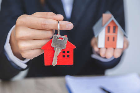 Businessman's hand holds house keys, house and real estate trading ideas.
