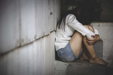 A woman hiding face. Violence against women concept. Depressed teenager sitting holding head in hands, stressed sad young woman having mental problems. Stock Photo