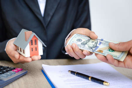 Hands giving house model to other hands with money. Concept of real estate and deal. Stock Photo