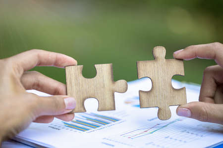 Two hands of businessman to connect couple puzzle piece. symbol of association and connection. business strategy. Stock Photo