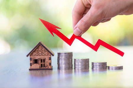 Hand  holding graph over the Increasing house miniature. Property investment and house mortgage financial concept, Investment property, Real estate, Saving money. Stock Photo