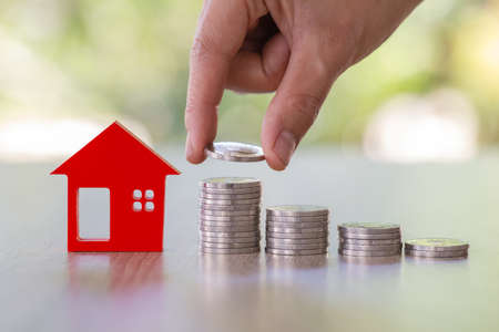 Hand putting money coin stack with small house, purchase of habitation, buy a house,Risk, Assets, Property Investment, Saving money for property investment concept.