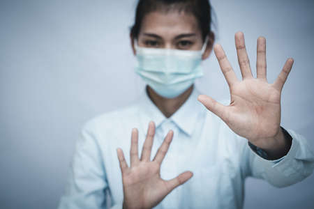 Girl wearing mask for protection from disease and show stop hands gesture for stop  virus outbreak.