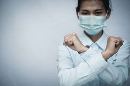 Girl wearing mask for protection from disease and show stop hands gesture for stop virus outbreak. Stock Photo