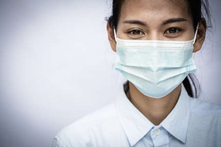 Woman wearing mask, covering face to prevent contagious disease, COVID 19, Coronavirus, Portrait of a woman in a medical mask. Young woman patient, copy space