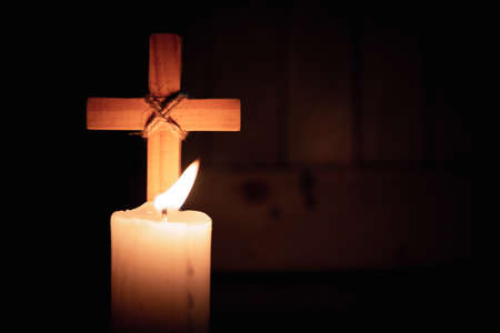 Wood cross by candlelight.