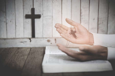 Hand of woman while praying for christian religion, Casual woman praying with a cross, Religion concept.