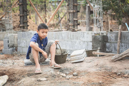 Concept of poverty and child labor, Children who are working on construction sites , Against child labor, Poor children, construction work, Violence children and trafficking concept 版權商用圖片