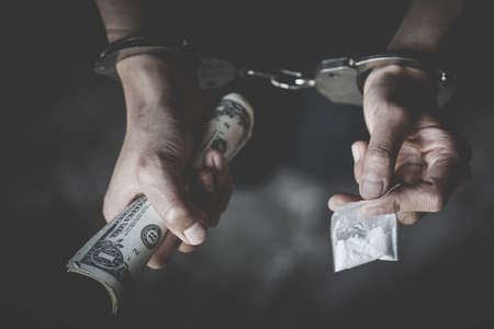 The drug dealer was arrested in handcuffs, drugs money  in concept about danger and threat of the drug. International Day against Drug Abuse and Illicit Trafficking