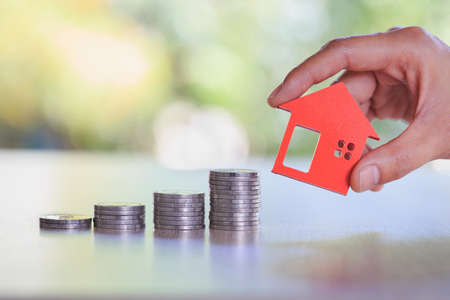 Hands holding a  house model. Housing industry mortgage plan and residential tax saving strategy, mortgage, investment, real estate and property concept