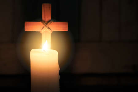 The candle glows in front of the cross. Christmas, Easter and religious background with copy space. Stock fotó